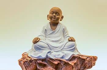 a figure of a little monk in meditation